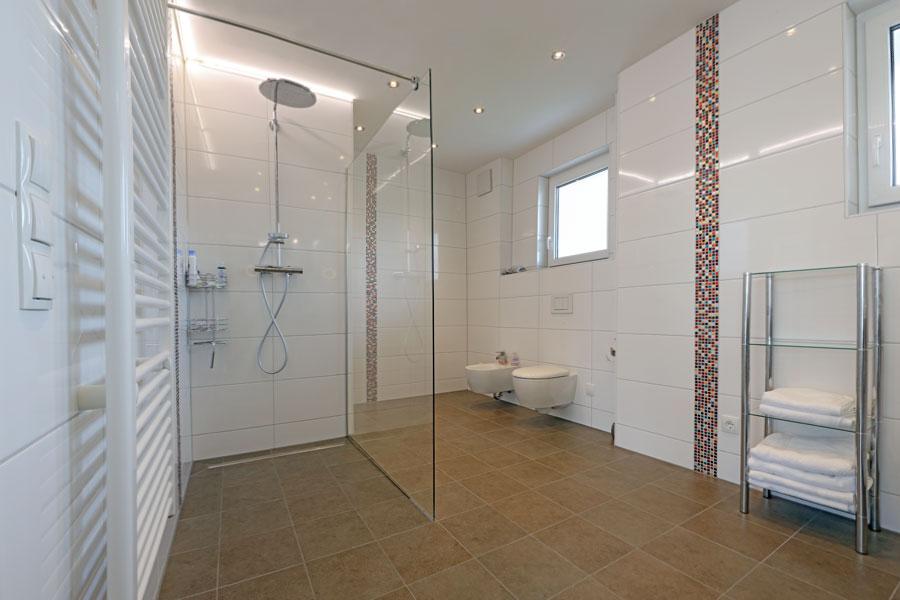 Barrierefreie, raumhoch geflieste Badezimmer und Duschbereiche mit mittig angeordnetem Bodenablauf